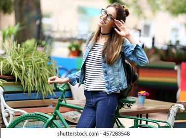 Smiling young woman posing with bicycle