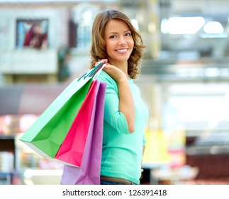 Smiling young woman posing with a handful of shopping bags