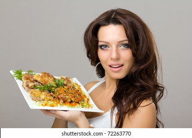 smiling young woman posing with a meal on a gray background