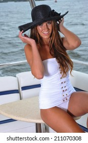 Smiling young woman posing on the luxury yacht wearing white swimsuit and hat.