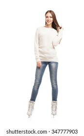 Smiling young woman posing in pair of ice skates over white background