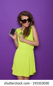 Smiling young woman posing with smart phone. Three quarter length studio shot on violet background.