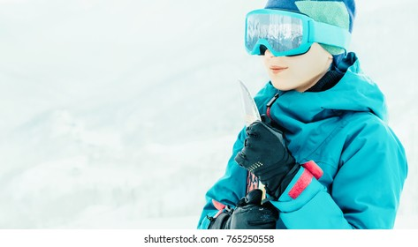 Smiling young woman in protective sunglasses standing with snowboard outdoor. Snowy mountains reflected in glasses.
