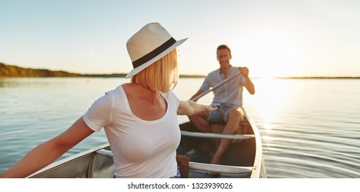 Smiling young woman reaching back to her boyfriend while paddling a canoe together on a lake on a late summer afternoon