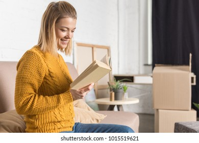 smiling young woman reading book while moving home