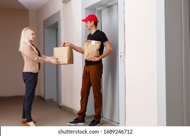 Smiling Young Woman Receiving Groceries From Delivery Man At apartment