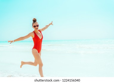 smiling young woman in red beachwear on the beach jogging