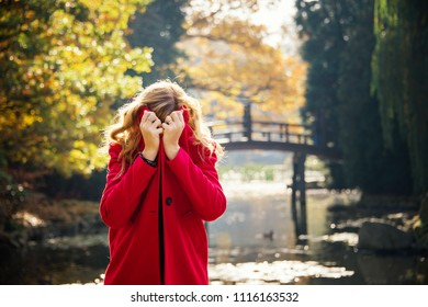 Smiling young woman in red coat in autumn city park near lake