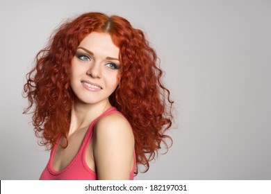 Smiling young woman with red hair on gray background.