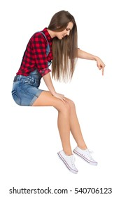 Smiling young woman in red lumberjack shirt, jeans shorts and white sneakers sitting on a top, pointing down and looking. Side view. Full length studio shot isolated on white.