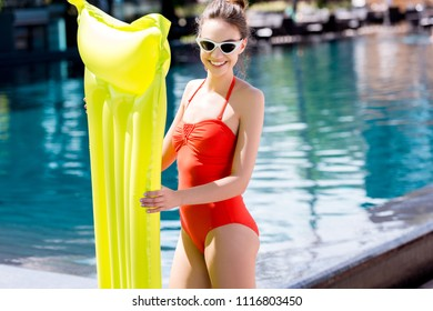 smiling young woman in red swimsuit with inflatable mattress standing at poolside and looking at camera