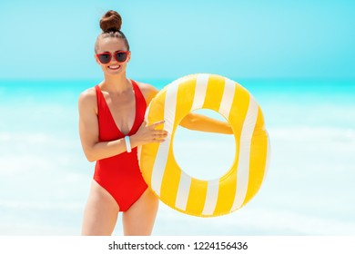 smiling young woman in red swimsuit with yellow inflatable lifebuoy on the seacoast