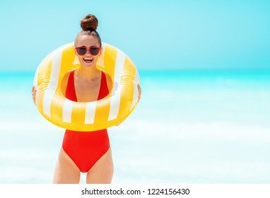 smiling young woman in red swimwear on the seashore wearing yellow inflatable lifebuoy