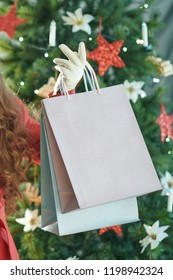 smiling young woman in red trench coat near Christmas tree showing shopping bags and Christmas present box