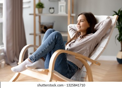 Smiling young woman relaxing leaning back in comfortable chair at home, happy girl resting with hands behind head in cozy armchair, dreaming about good future, looking in distance