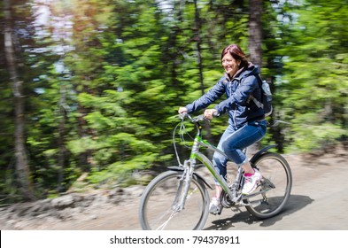 Smiling Young Woman Riding a Bicycle on a Forest Road on a Sunny Spring Day. Motion Blur.