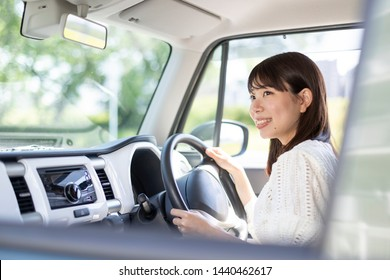 Smiling young woman riding a car