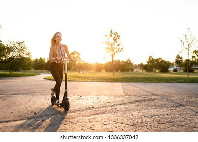 Smiling young woman riding push scooter, full-length shot.