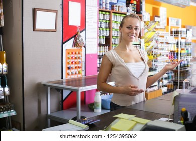 smiling young woman seller standing at the counter in housewares store