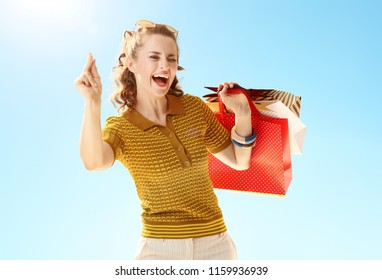 smiling young woman with shopping bags fingers snapping against blue sky