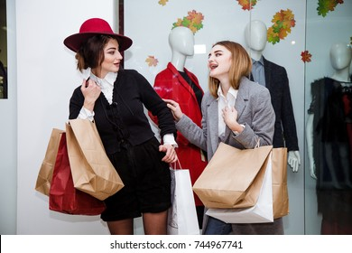 Smiling young woman with shopping bags over mall background. Happy girl buy clothes with discounts.