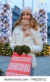 Smiling young woman shopping for Christmas wearing warm winter clothes holding shopping bags.