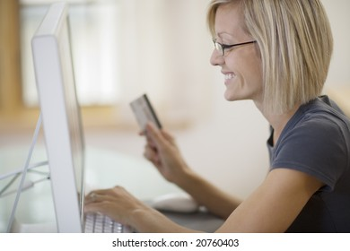 Smiling young woman shopping on-line with credit card and computer