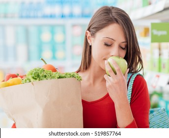 Smiling young woman shopping at the supermarket, she is holding a grocery bag with fresh organic vegetables and smelling an apple