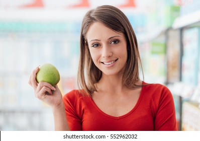 Smiling young woman shopping at the supermarket, she is holding a fresh apple, food freshness and diet concept