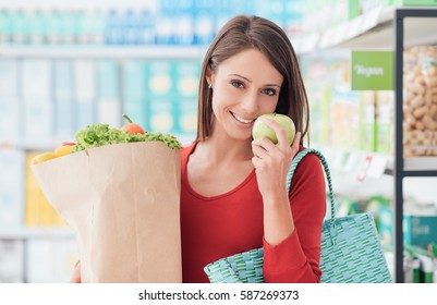 Smiling young woman shopping at the supermarket, she is holding a grocery bag with fresh organic vegetables
