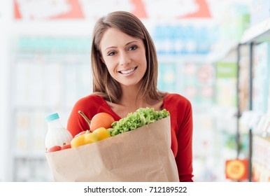 Smiling young woman shopping at the supermarket and holding a grocery bag with fresh vegetables, lifestyle and retail concept