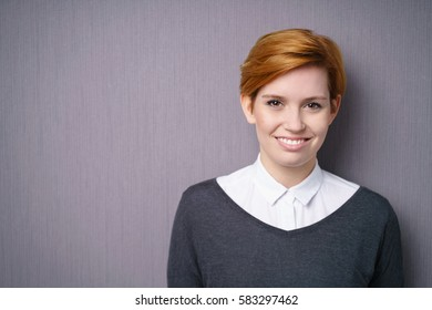 Smiling young woman with short red hair wearing white blouse under dark sweater, looking at camera standing against purple wall with vignette effect and copy space