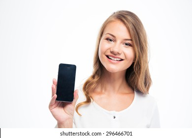 Smiling young woman showing blank smartphone display isolated on a white background. Looking at camera