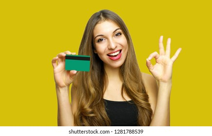 Smiling young woman showing credit card and showing OK sign over yellow background