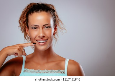 Smiling young woman showing her perfect white teeth with braces. Looking at camera. Copy space.