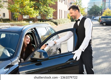 Smiling Young Woman Sitting In Car And Giving Car Key To Valet