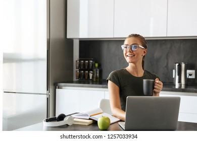 Smiling young woman sitting at the kitchen, using laptop computer for study, holding cup
