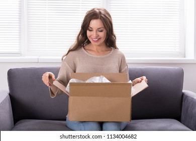 Smiling Young Woman Sitting On Sofa Unpacking Received Parcel