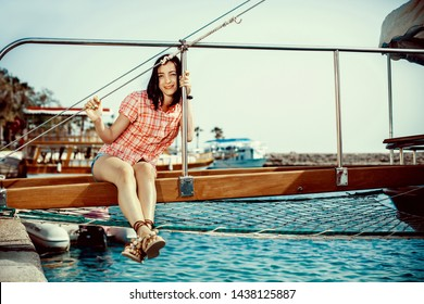 Smiling young woman sitting on sailboat, enjoying mild sunlight, sea or river cruise, summer vacation and travel concept
