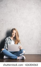Smiling young woman sitting on wooden floor against concrete wall and using laptop