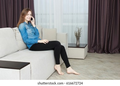 Smiling Young Woman Sitting On Couch Talking On Phone.