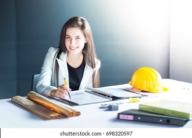 Smiling young woman sitting on office desk and looking to camera.