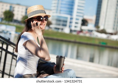 Smiling young woman sitting outdoors with a cup of coffee and talking on the phone
