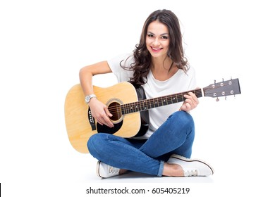 Smiling young woman sitting and playing guitar isolated on white