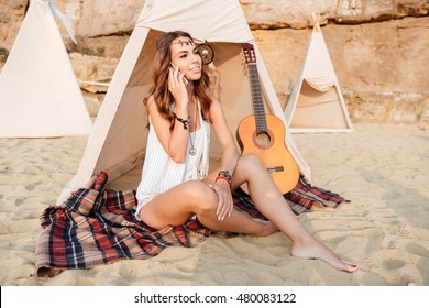 Smiling young woman sitting and talking on cell phone in teepee on the beach