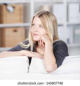 Smiling young woman sitting thinking relaxing with her arms over the back of a sofa leaning on the top