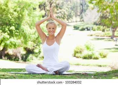 Smiling young woman sitting in a yoga position outdoors