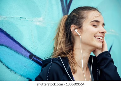 Smiling young woman with smartphone and headphones listening to music outdoor
