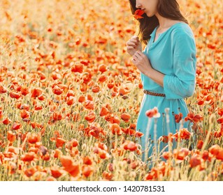 Smiling young woman smelling a red poppy in flower meadow on summer nature.
