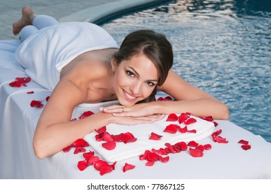 Smiling young woman at spa with pool in the background